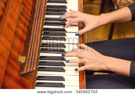 Hands Of A Female Pianist With Blue Nail Polish On The Nails On The Keys Of A Piano. Girl Playing Th