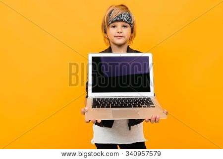 European Boy Holds A Laptop With The Screen Forward With Mockup On A Yellow Background.