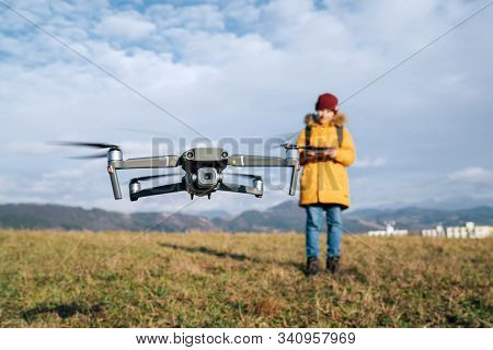 Close Up Image Of Flying Drone With Teenager Boy Dressed Yellow Jacket  On Background Piloting A Mod