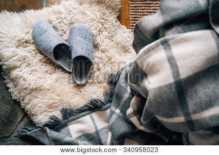 The Pair Of Gray Home Slippers Near The  Bed On The White Sheepskin In The Cozy Bedroom. Home Sweet
