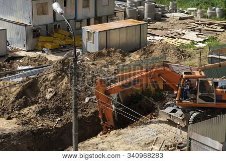 Work Excavator At A Construction Site. An Orange Excavator Digs The Ground, There Are Trailers For B