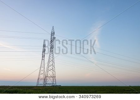 Pair Of Transmission Towers Against A Prairie Sunrise
