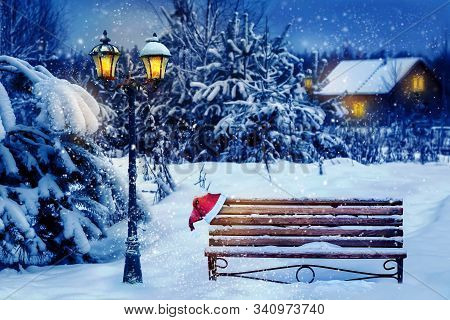 Christmas Art Card. Santa Hat On A Bench In The Snow Against The Background Of The Christmas Winter