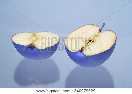 A Blue Apple Cut In Half On A Light Blue Background. The Two Halves Of The Fruit.