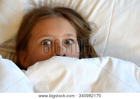 The Girl Is Hiding Under The Covers In Bed. Children Are Afraid Of Nightmares. Unhealthy Baby Sleep.