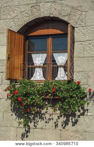 Glazed Window With Flowers And Wood Shutters In A Country House With Stone Wall Near Bento Goncalves