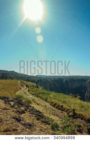 Dirt Pathway And People At The Itaimbezinho Canyon With Steep Rocky Cliffs And Sunlight Near Cambara