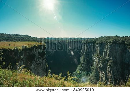 Itaimbezinho Canyon With Steep Rocky Cliffs On A Flat Plateau And Sunlight Near Cambara Do Sul. A Sm