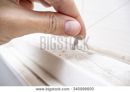A Hand Taking A Piece Of Dust From Furniture, Dusty Home House Concept.