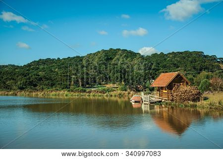 Small Rustic Shack Reflected On The Lakeside Of Crystal Clear Water And Hills Covered By Grove Near