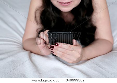 Happy Woman With Long Curly Hair Lying On A Bed And Using Smartphone. Mobile Phone In Female Hands,