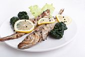 serving of grilled Blue whiting fish with lemon, pepper and fried spinach poster