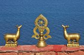 Wheel of teachings and deers on roof of Buddhist temple in Tibet (with waters of Manasarovar lake background) poster