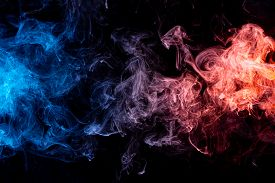 Abstract Art Blue And Red Colored Smoke On Black Isolated Background. Stop The Movement Of Multicolo
