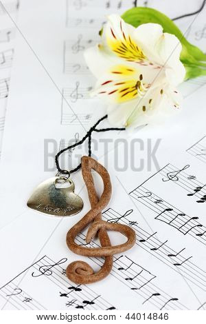 Treble clef, pendant and flower on musical background