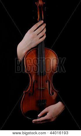 Violin in hands on black background