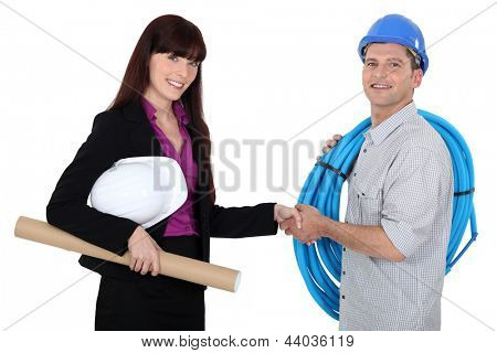 Female architect shaking electrician's hand