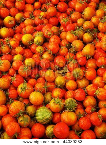 Pile of Red Juicy  Small Heirloom Tomatoes with softer background at the farmers market