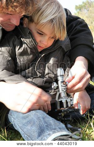 Father and using using microscope in a field