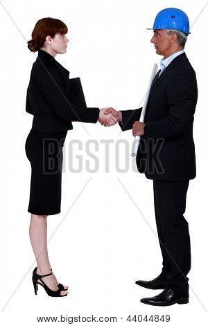An architect and a businesswoman shaking hands.