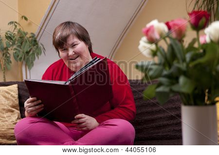 Mentally disabled woman is reading a book and smiles poster