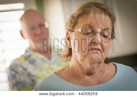 Senior Adult Couple in Dispute or Consoling in Kitchen of House.