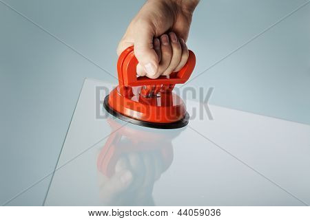 Man lifting a sheet of glass using a vacuum suction cup tool aka dent puller.