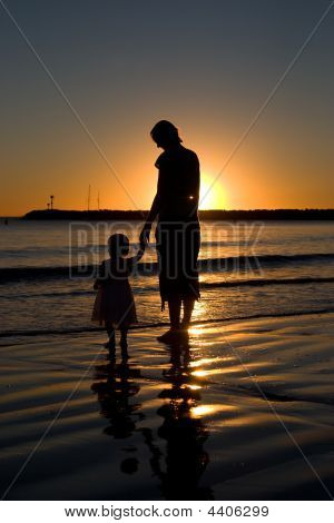 Silhouette of mother and daughter on the beach at sunset. Back lit by the setting sun. poster