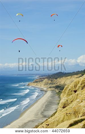 Hang Gliders Above Ocean and Cliffs