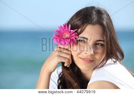 Portrait Of A Beautiful Woman On The Beach With A Pink Flower