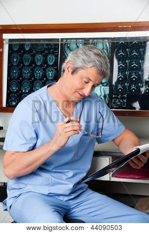 Mature male medical professional in uniform reading document at clinic