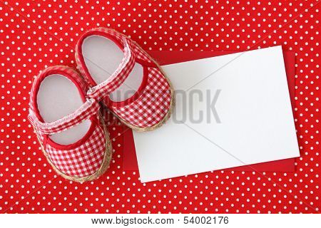 Baby shoes and blank note on spotted background