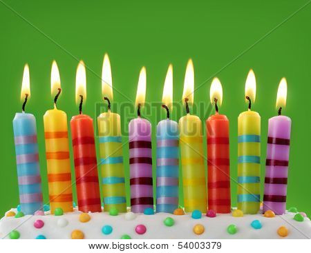 Ten colorful candles on green background