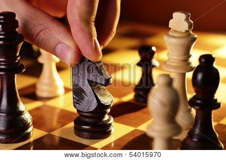 Mans Hand Playing A Game Of Chess