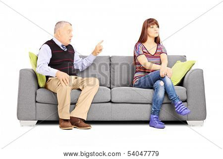 Father reprimending his uninterested daughter seated on a couch isolated on white background poster