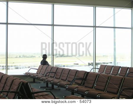 a lone man waits in an empty airport departure lounge. poster