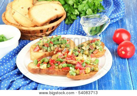 Sandwiches with vegetables and greens on plate on wooden table close-up