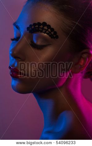 Moody seductive portrait in purple lighting of a beautiful woman with her eyes closed and pouting sensual lips , closeup head shot in profile