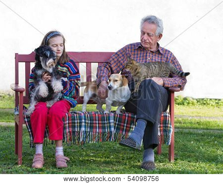 Girl and her grandfather sitting in garden with dogs and cat poster