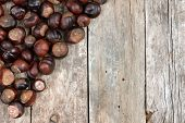 Closeup chestnuts on wooden desk, background . poster