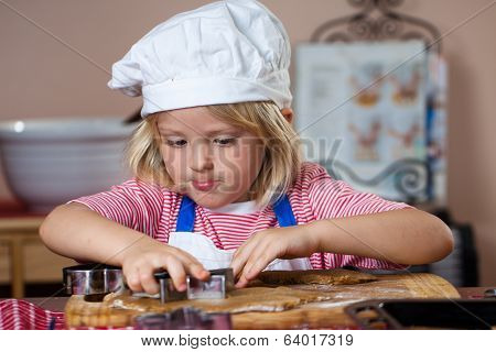 Cute Boy Cutting Out Gingerbread Shapes