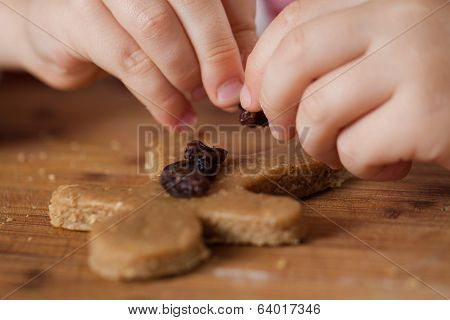 Child Putting Raisins On Gingerbread Man