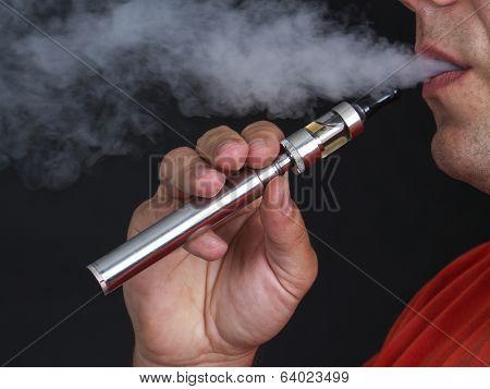 Closeup of man using e-cigarette and exhaling vapor shot over black background poster