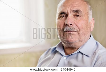 Retired Senior Man Looking Pensively At The Camera