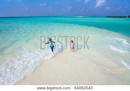 Above view of a stunning tropical ocean and white sand beach with kids plashing at shore