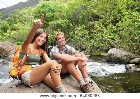 Hiking people in outdoor activity wearing backpacks relaxing. Hikers, woman and man hiker looking with smiling happy. Healthy lifestyle image from Iao Valley State Park, Wailuku, Maui, Hawaii, USA.