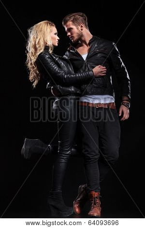 full length portrait of a young man and woman embracing and looking into each other's eyes. on black background