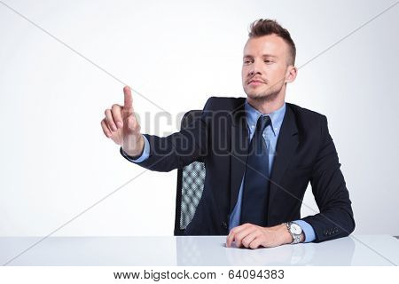 young business man sitting at the desk and pushing an imaginary button in front of him. on a light gray studio backgroud