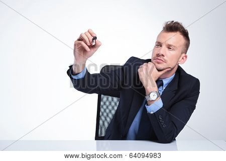 young business man at the desk writing something with his marker on an imaginary screen while holding a hand at his chin in a pensive manner. on a light gray studio background