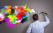 Businessman painting abstract colorful design on gray background concept for  business creativity, imagination and inspiration poster